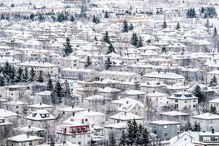 Snow gleams over the houses in Reykjavik and the midnight sun shines above them
