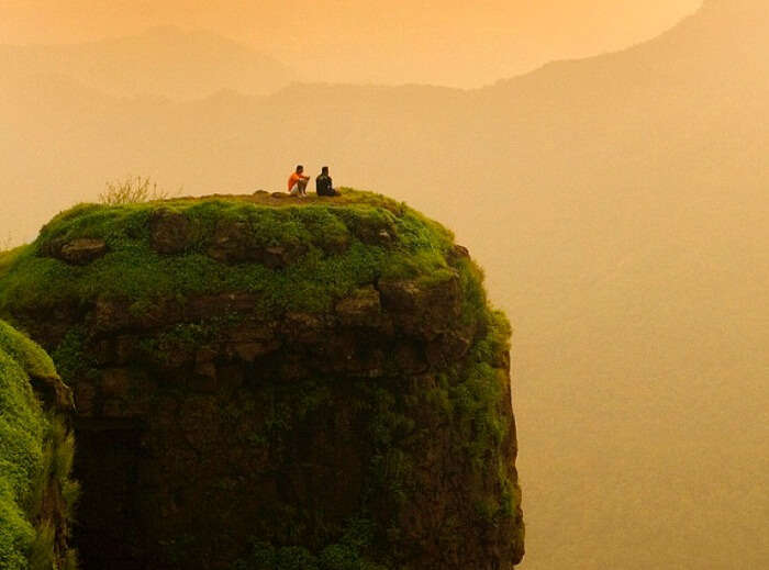 Two friends enjoy the beautiful sunset at the Porcupine Point at Matheran