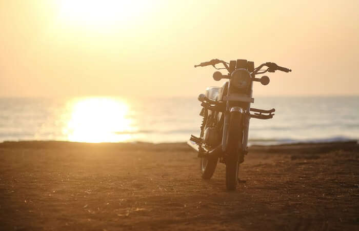 a lone bike on the beach on a road trip from mumbai to goa