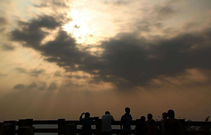 A group gathers to see the sunset at the popular Agumbe Sunset Point in Karnataka