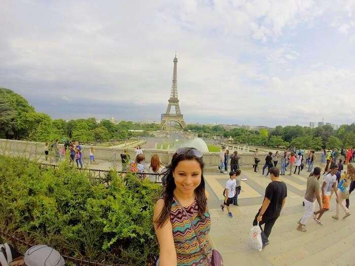 Leena in the background of the Eiffel Tower in Paris