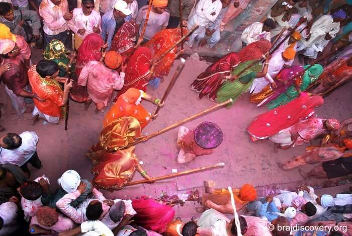 A group of women playfully beating a man with stick during Mathura Holi