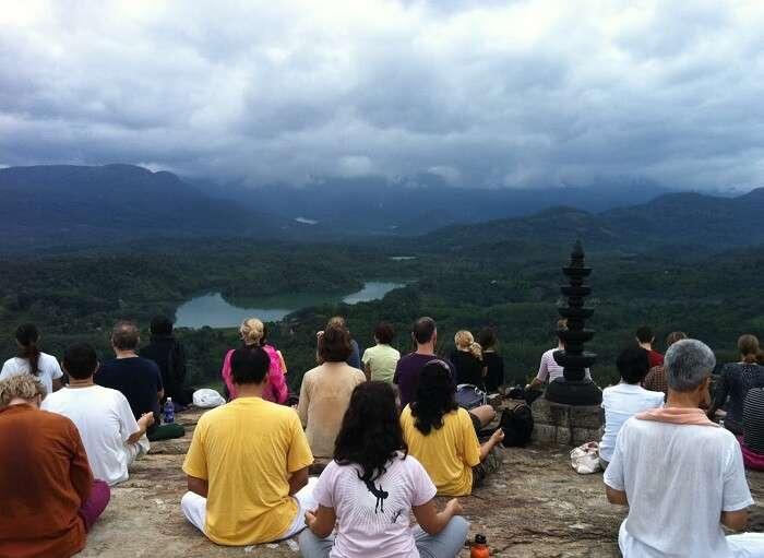 Various people enjoying the serene yoga on Neyyar Dam in Kovalam