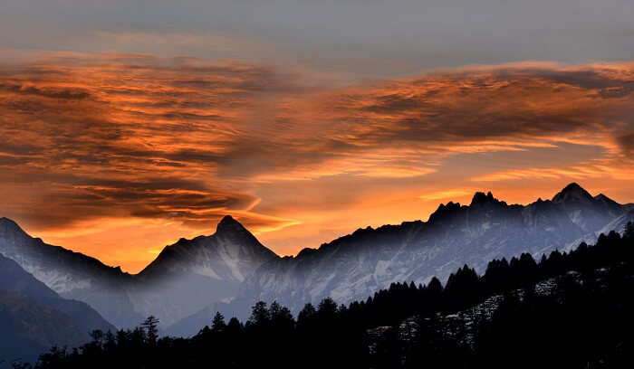Fiery orange hues of sunrise in the hills of Auli