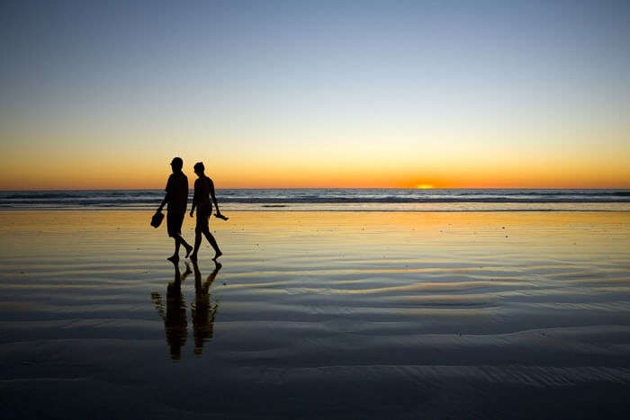 Couple walk by the Besant Nagar Beach while the sun sets
