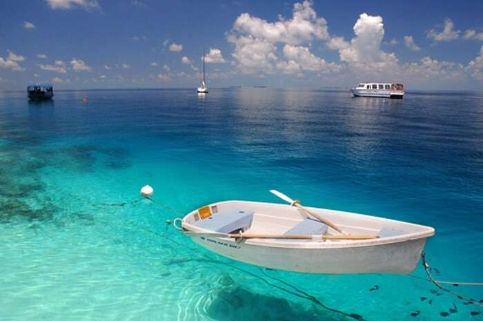 A boat parked in the turquoise waters near the Fihalhohi Island
