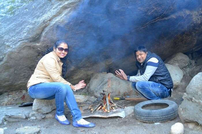 Madhumita and her husband near a bonfire in Manali