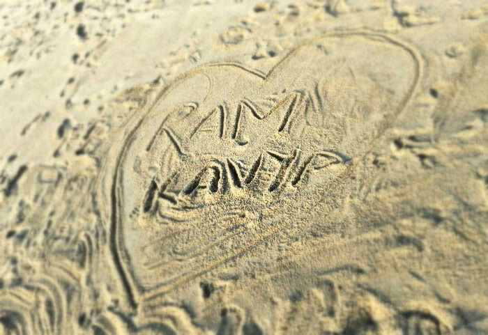 The names of Kavya and Ram on the beach