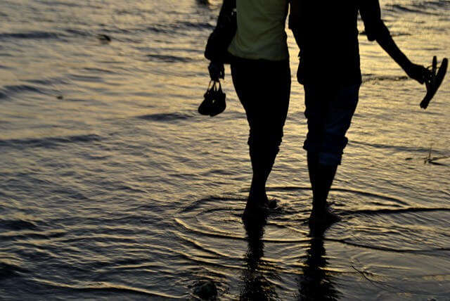 A couple enjoys sea water at Marina Beach