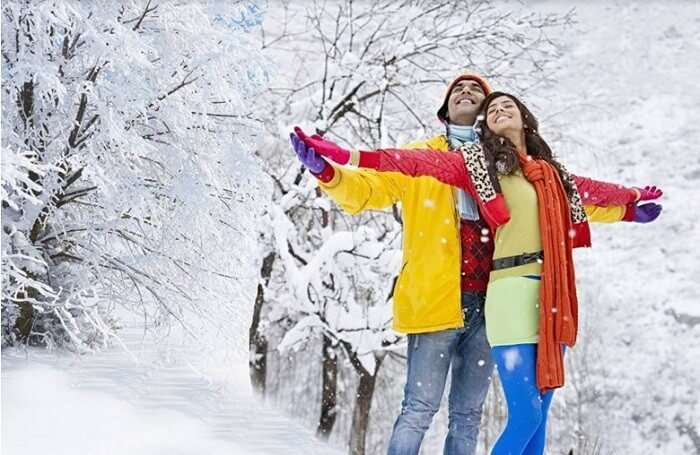 Honeymooners enjoying snowfall in the romantic hill station of Manali