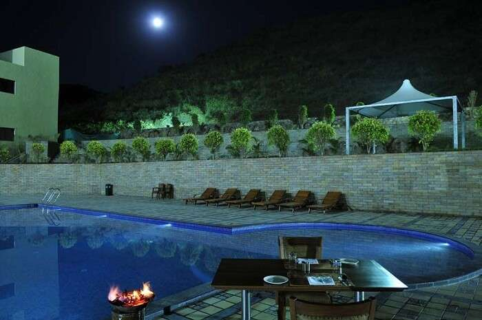 A moonlit night view of the swimming pool at the Cambay Resort