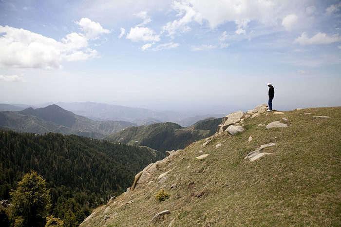 A man looking down from Dainkund Peak in Dalhousie