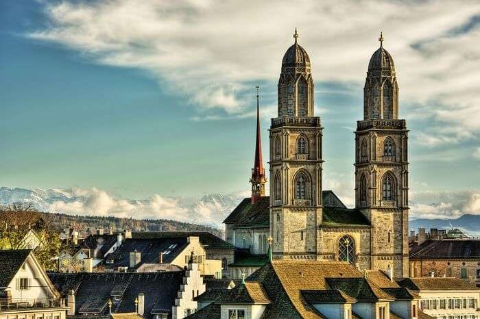 The twin towers of the Grossmunster Churche with the cloud-covered Alps in the background
