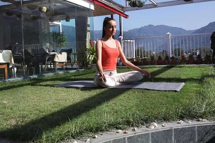 A tourist takes a yoga-cum-meditation session at the Ell Bee Resort in Rishikesh