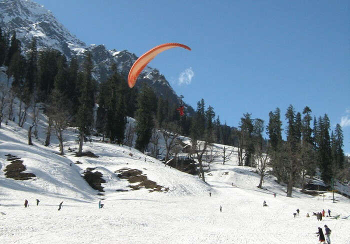 A tourist tries paragliding in the snow-clad Solang valley
