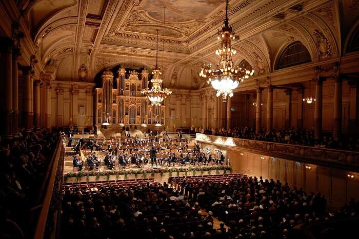A vast audience attending a concert performed by 100 musicians at the Zurich Tonhalle