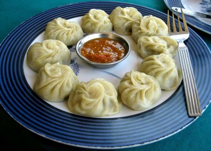 A plate full of momos and red chutney served at various food stalls in Kasauli