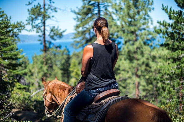 A woman solo traveler riding a pony through the trees
