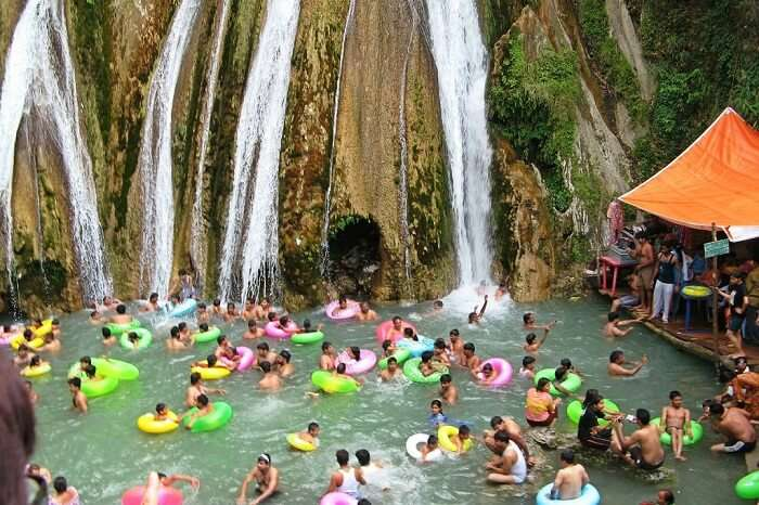 People bathing and enjoying the chilling water of Kempty Waterfalls