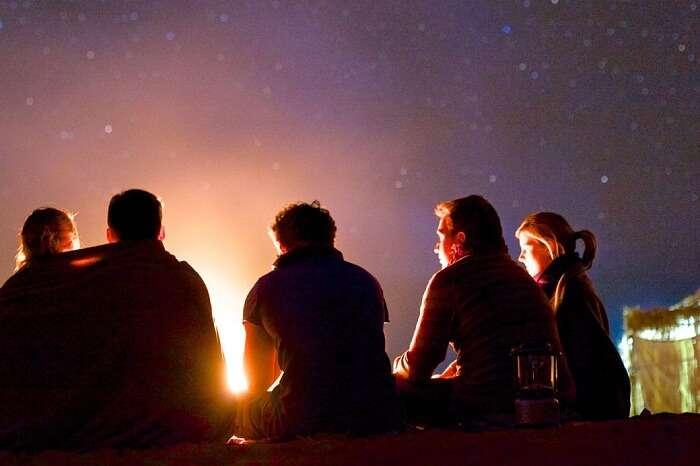 Travelers enjoying bonfire in Munnar