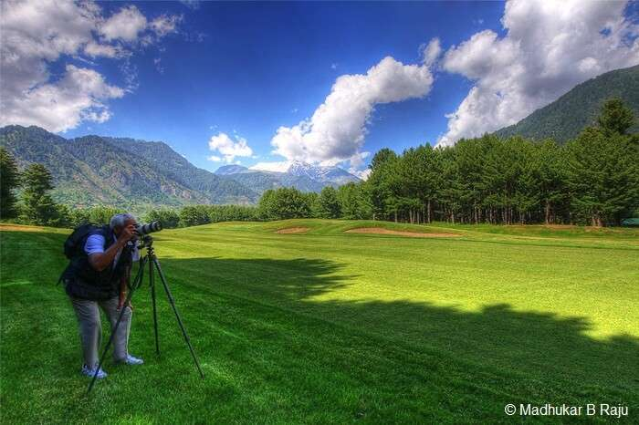 A photographer gets ready to take a snapshot at the Gulmarg Golf Course