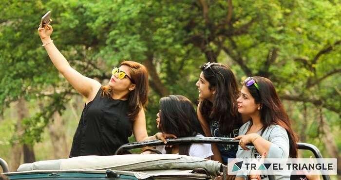 Girls click a selfie on a safari jeep