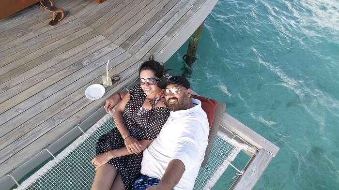 Angad and his wife sit by the ocean in Maldives