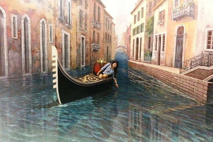 A tourist blends in the 3D painting at the Art In Paradise