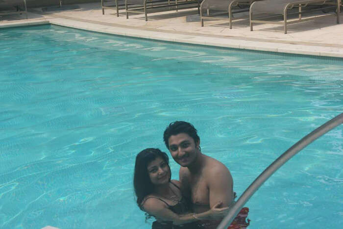 Mitula and his wife take a swim in the pool of their resort
