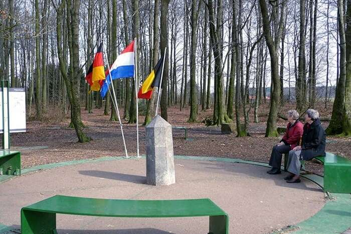 Tourists sit at the round seating arrangement at the border of Germany-Netherlands-Belgium