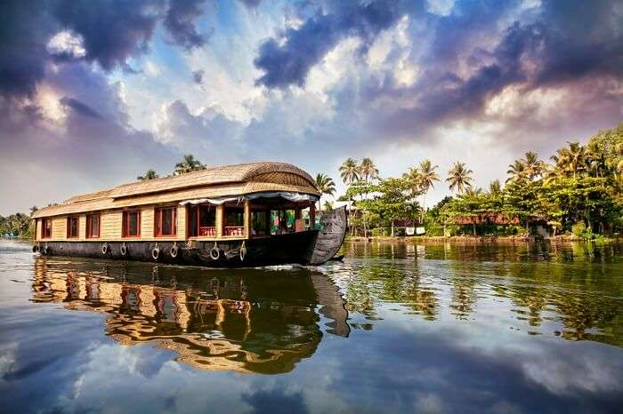A houseboats in Alleppey traversing the deep blue backwaters