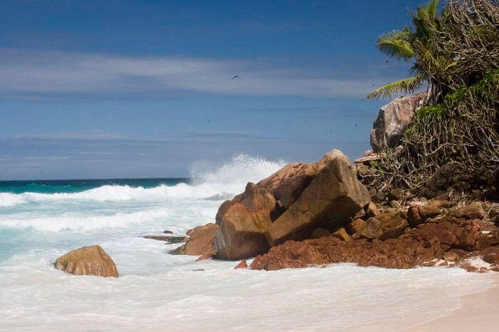 The waves slashing against the large boulders at a beach on Aride Island