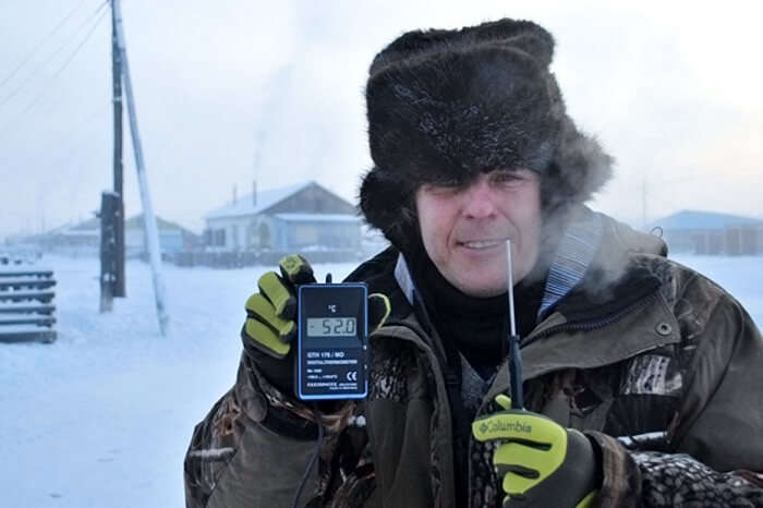A weather specialist showing the low temperature in Oymyakon during winters