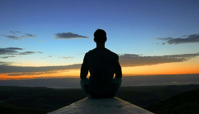 silhouette of a man sitting in a meditative pose