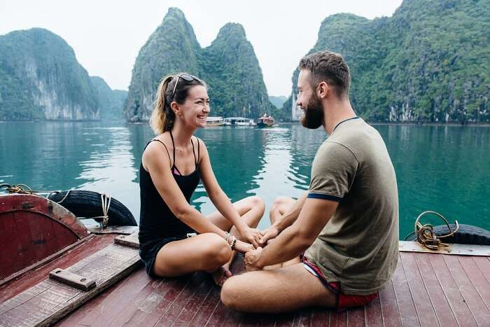 Couple holding hands and smiling on the deck of cruise ship at Ha long Bay