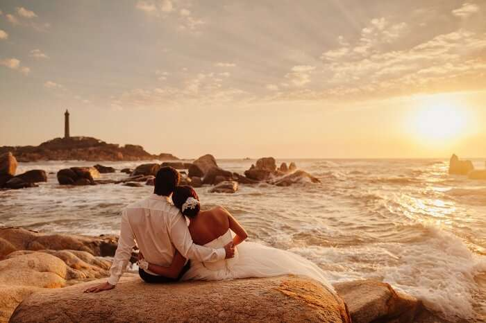 Couple enjoys a sunset view opposite to the lighthouse in Vietnam