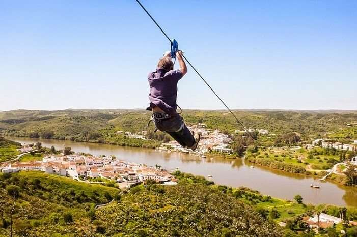 A person ziplines across the border of Spain and Portugal