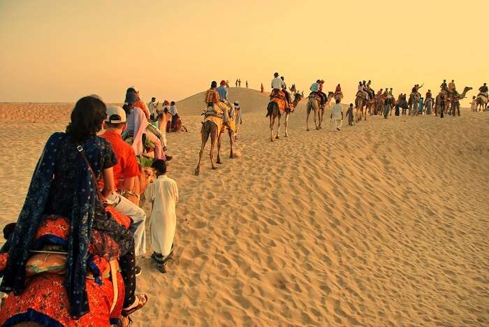 Happy tourists enjoying camel safari in Rajasthan