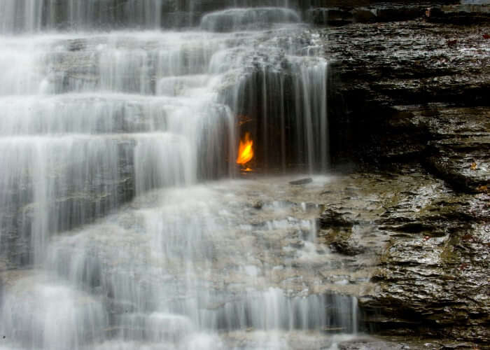 Mysterious eternal flame burning under the waterfall