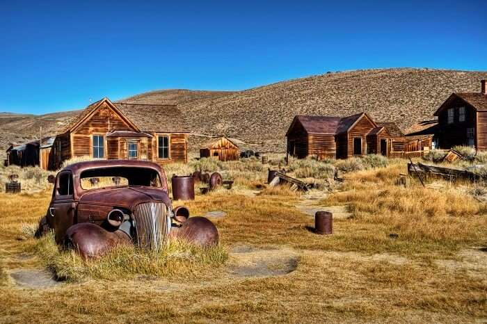 A photo capturing an old car and ruins of the houses in the abandoned town of Bodie in California