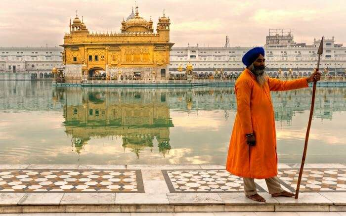 Sikh man standing in front of Golden Temple in Amritsar best place to visit in November in India