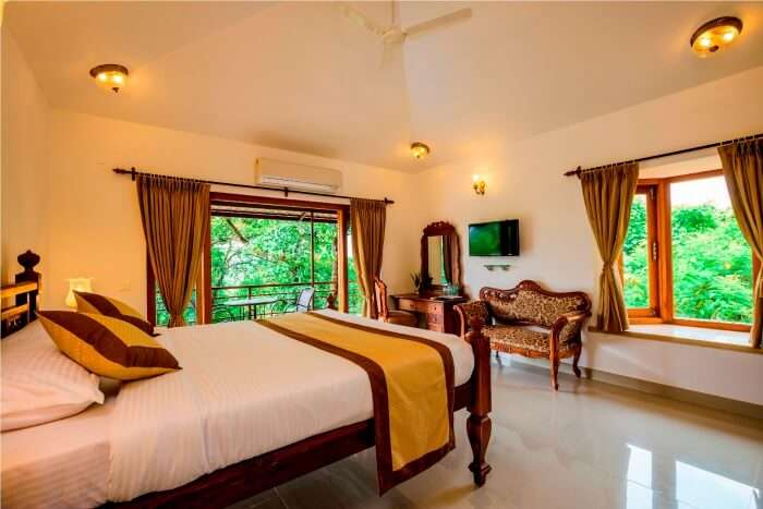 A bedroom with a garden view of Highland Heritage Goa