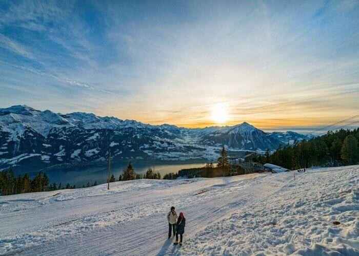 Two friends enjoying the amazing vistas of sunrise over Interlaken