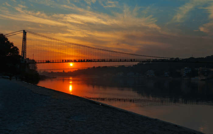 View of River Ganga and Ram Jhula bridge at sunset. Rishikesh. India