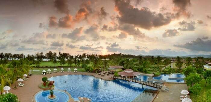 The landscaped gardens and poolside deck of the The Lalit Golf & Spa Resort Goa