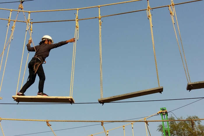 Adventurer performing plank walk at Rope Castle Adventure Park