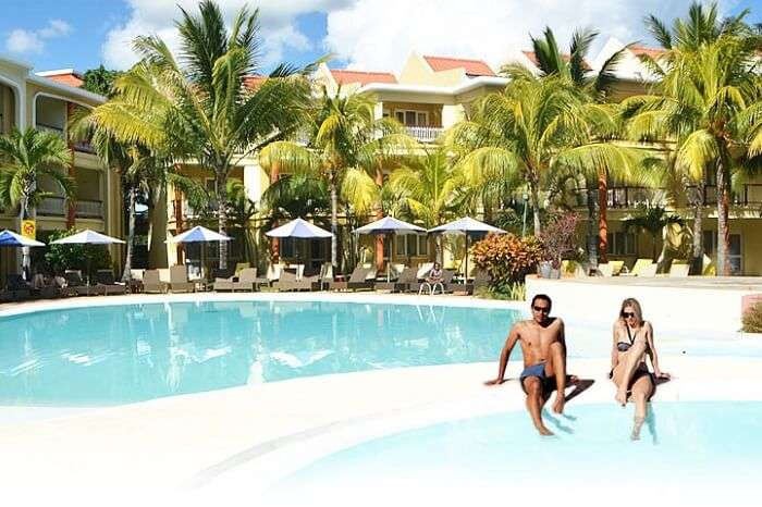 A couple relaxes at the swimming pool at the Tarisa Resort in Mauritius