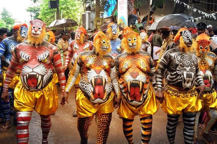 Participants of the parade walk with tiger masks and painted bodies during the Athachamayam Festival