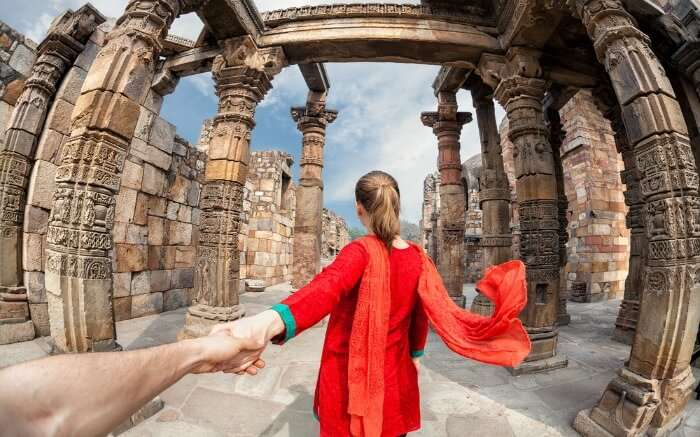 Foreigner at Qutub Minar Delhi wearing a red suit