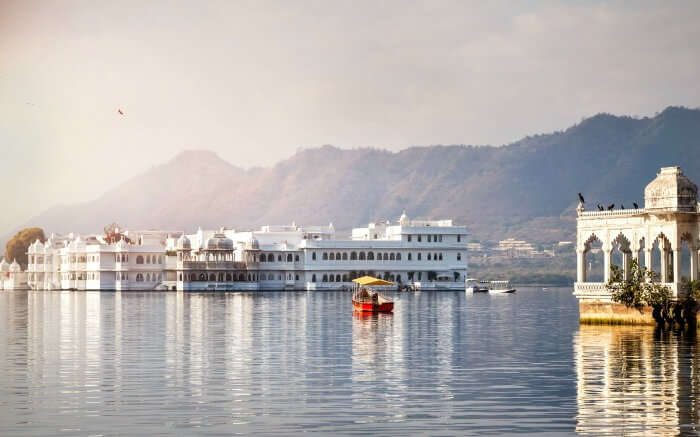Tourists enjoying boating on Lake Pichola - in the backdrop of City Palace